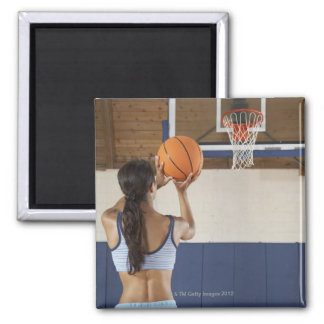 Woman aiming at hoop with basketball, rear view square magnet