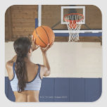 Woman aiming at hoop with basketball, rear view square sticker