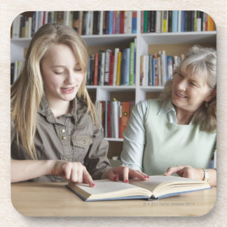 Woman and granddaughter reading together beverage coasters