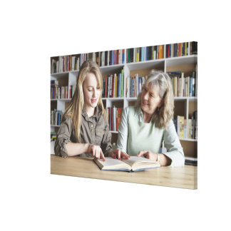 Woman and granddaughter reading together canvas print