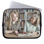 Woman and granddaughter reading together computer sleeve