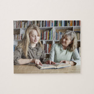Woman and granddaughter reading together jigsaw puzzle