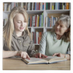 Woman and granddaughter reading together large square tile