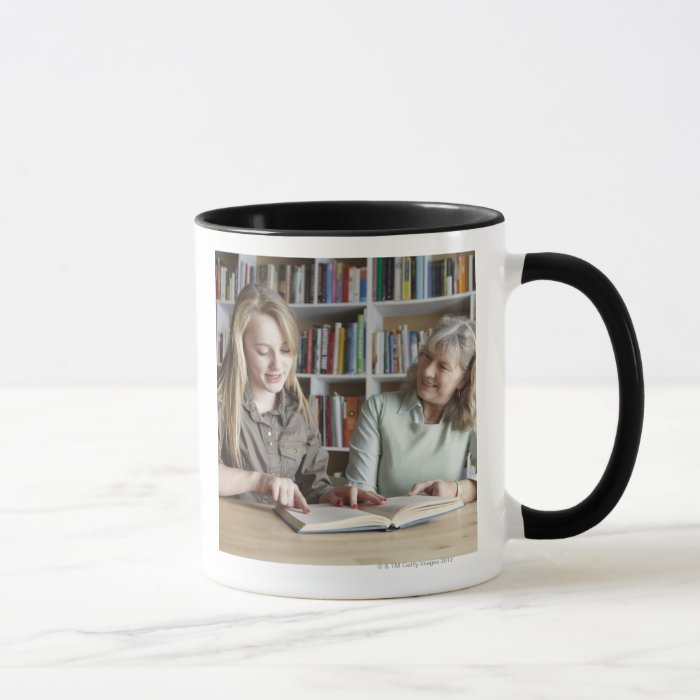 Woman and granddaughter reading together mug