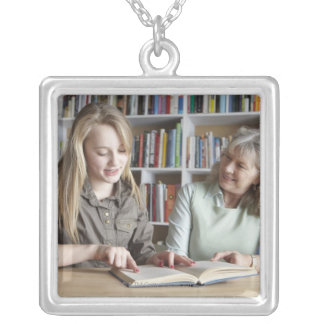 Woman and granddaughter reading together silver plated necklace