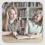 Woman and granddaughter reading together square sticker