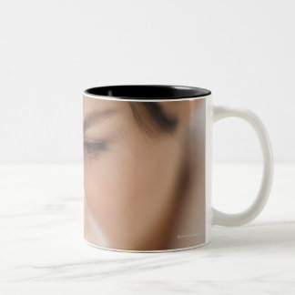 Woman blowing her nose. Two-Tone mug