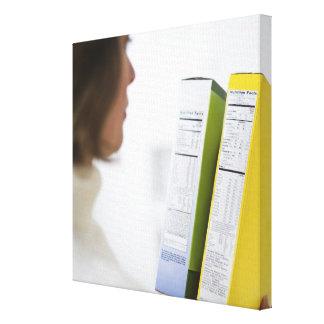 Woman comparing nutrition labels canvas print