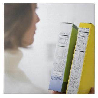 Woman comparing nutrition labels large square tile