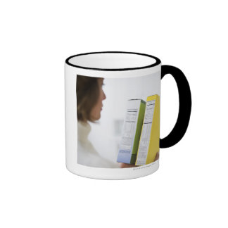 Woman comparing nutrition labels coffee mugs