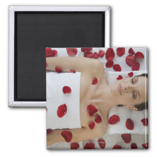 Woman covered in flower petals laying on massage square magnet