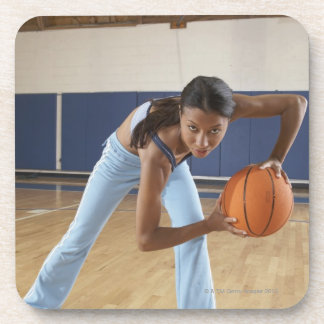 Woman crouching with basketball, portrait coaster