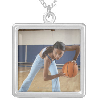 Woman crouching with basketball, portrait silver plated necklace