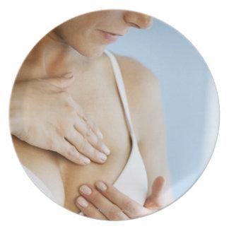Woman doing breast self exam 2 plate