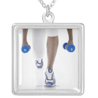 Woman doing lunges with dumbbells (low section) square pendant necklace