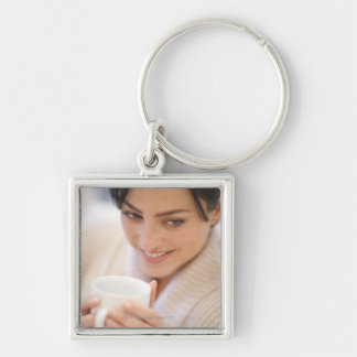 Woman drinking a hot drink. Silver-Colored square key ring