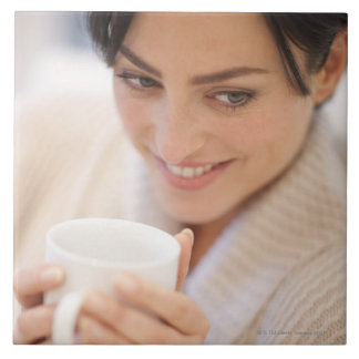 Woman drinking a hot drink. tile