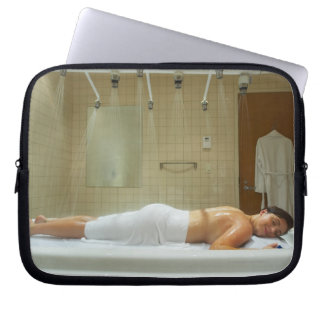 Woman enjoying hydrotherapy in vichy shower laptop sleeve