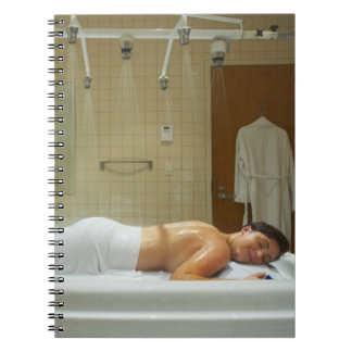 Woman enjoying hydrotherapy in vichy shower notebooks