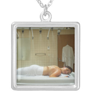 Woman enjoying hydrotherapy in vichy shower silver plated necklace