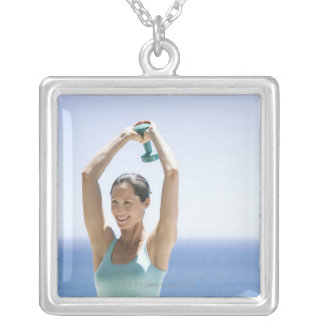 woman excercising with weights on her roof silver plated necklace