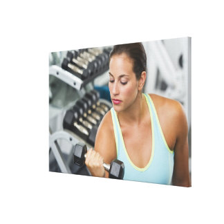 Woman exercising with dumbbells canvas print