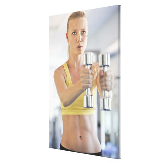 Woman exercising with weights canvas print