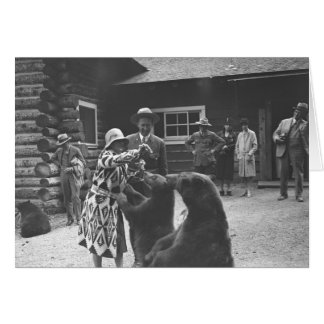 Woman feeding bears with a group of people in fron card