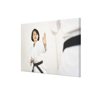 Woman fighting in karate competition canvas print