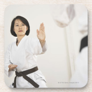 Woman fighting in karate competition coaster