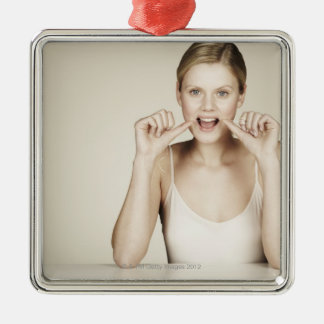 Woman flossing her teeth christmas ornament