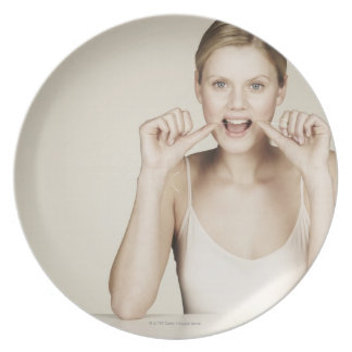 Woman flossing her teeth plate
