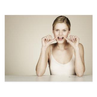 Woman flossing her teeth postcard