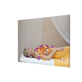 Woman getting a flower treatment at a spa. canvas prints