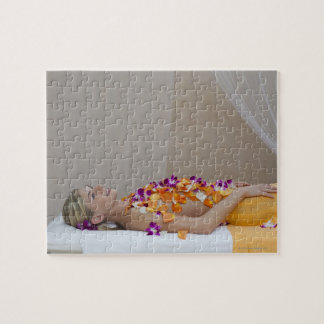 Woman getting a flower treatment at a spa. jigsaw puzzle