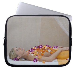 Woman getting a flower treatment at a spa. laptop sleeve
