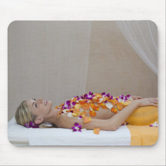 Woman getting a flower treatment at a spa. mouse mat