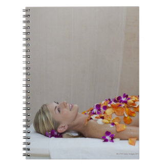 Woman getting a flower treatment at a spa. notebook