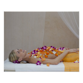 Woman getting a flower treatment at a spa. poster