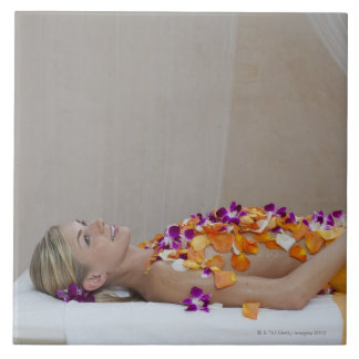 Woman getting a flower treatment at a spa. tile
