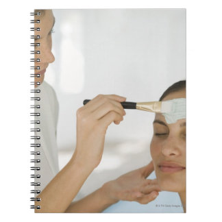 Woman getting beauty mud mask notebooks