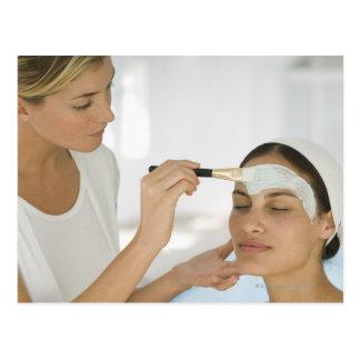 Woman getting beauty mud mask postcard