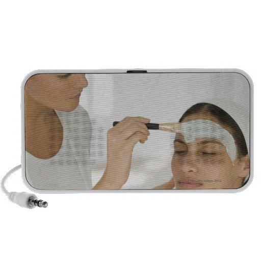 Woman getting beauty mud mask speaker system