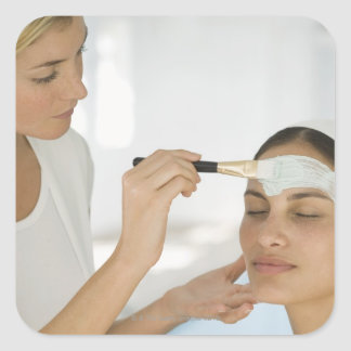 Woman getting beauty mud mask square sticker