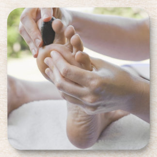 Woman getting foot massage with hot stone coaster