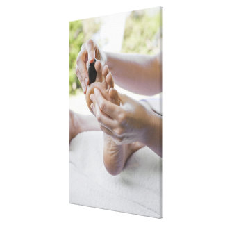 Woman getting foot massage with hot stone gallery wrapped canvas