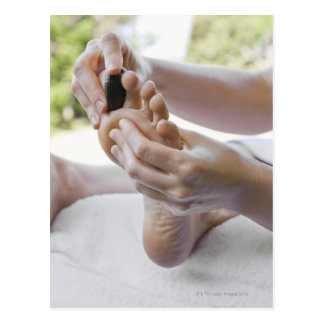 Woman getting foot massage with hot stone postcard