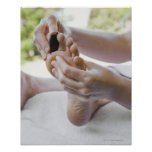 Woman getting foot massage with hot stone poster