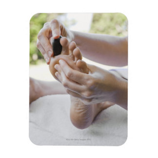 Woman getting foot massage with hot stone rectangular photo magnet