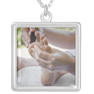 Woman getting foot massage with hot stone silver plated necklace